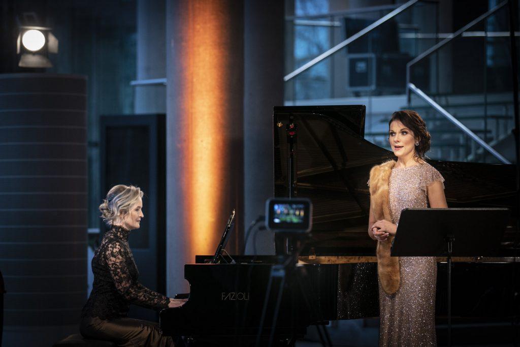 Koncert online z dolnego foyer Opery i Filharmonii Podlaskiej. Na zdjęciu dwie kobiety w długich sukniach. Jedna z nich gra na fortepianie. Druga stoi obok, śpiewa. Przed nimi kamera na statywie.