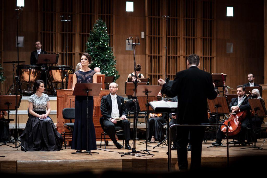 Na scenie siedzi orkiestra Opery i Filharmonii Podlaskiej. Z przodu, w długiej sukni stoi solistka. Przed nimi na podeście stoi dyrygent. Na końcu stoi duża choinka.