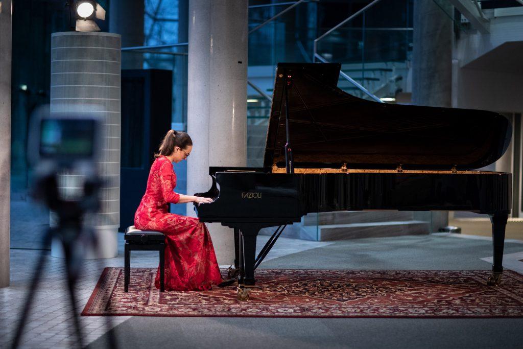Dolne foyer. Koncert online z cyklu ''Jesień z Chopinem'' Przy fortepianie kobieta w czerwonej sukni.
