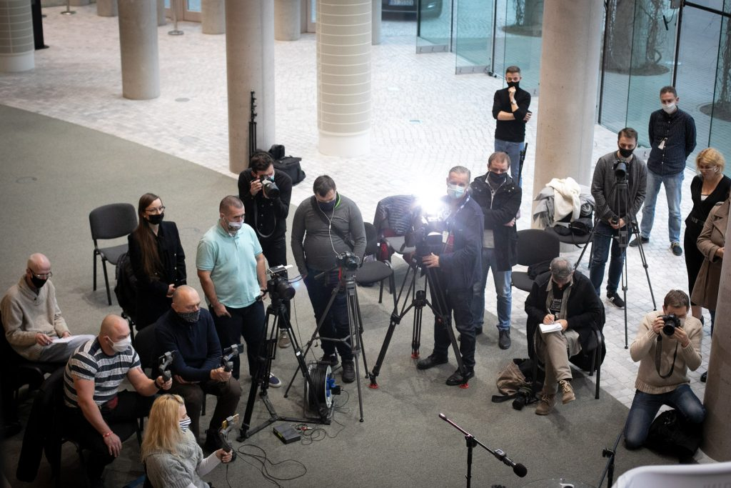 Kilkunastu dziennikarzy i reporterów zebranych podczas konferencji prasowej na dolnym foyer.