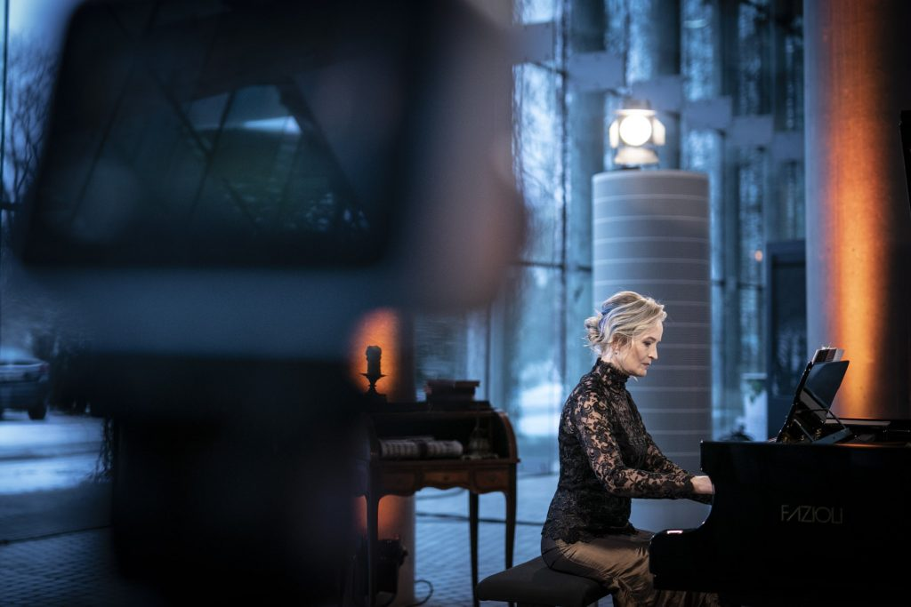 Koncert online transmitowany z dolnego foyer. Przy fortepianie siedzi kobieta w czarnej, koronkowej bluzce i ciemnozłotej, długiej spódnicy. Z przodu widać mocne zbliżenie na aparat na statywie.
