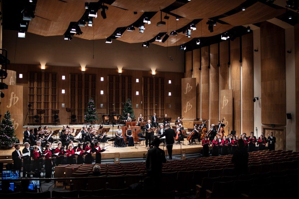 Na scenie gra Orkiestra Opery i Filharmonii Podlaskiej. Na środku siedzą dwie solistki. Przed sceną, po obydwu stronach stoi chór. Na widowni stoi kilka osób. Z tyłu stoi kilka choinek.