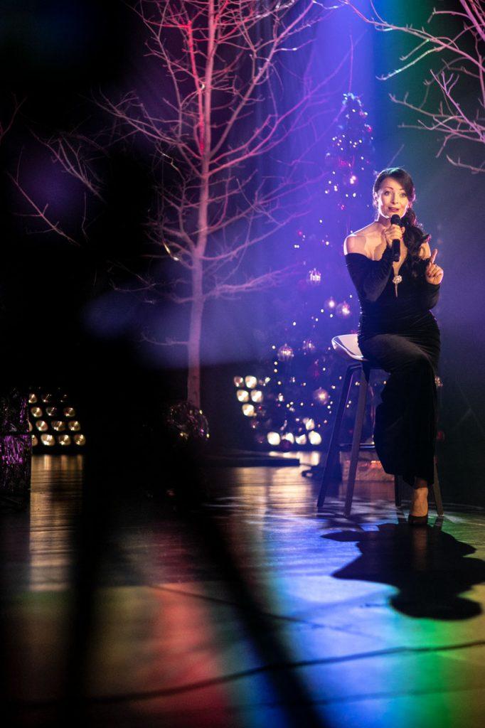 Scena w półmroku oświetlona kolorowym światłem. Na niej, na wysokim krześle siedzi kobieta w czarnej, długiej sukni. Śpiewa do mikrofonu. Za nią przystrojona w bombki i światełka choinka. Na środku drzewo bez liści.