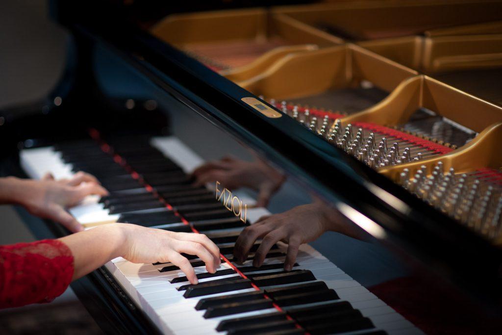 Zbliżenie na klawiaturę pianina na której gra kobieta w czerwonej sukni.
