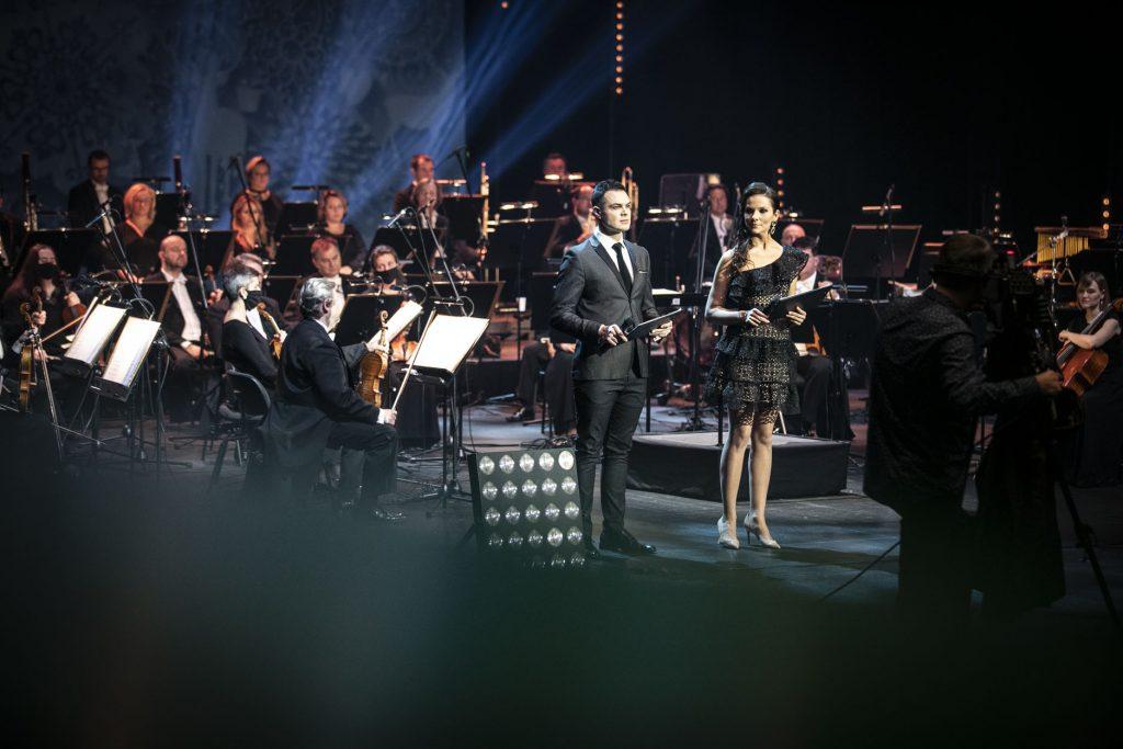 Nagranie koncertu ''Wielki kolędowanie''. Na scenie kobieta w czarnej sukience i mężczyzna w garniturze. Za nimi siedzi orkiestra. Z przodu stoi mężczyzna przy statywie z kamerą.