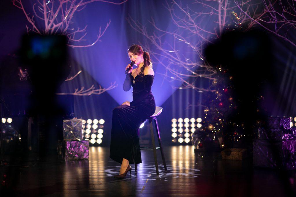 Scena w półmroku oświetlona niebieskim światłem. Na niej, na wysokim krześle siedzi kobieta w czarnej, długiej sukni. Śpiewa do mikrofonu. Po prawej stronie przystrojona w bombki i światełka choinka. Z tyłu drzewa bez liści.