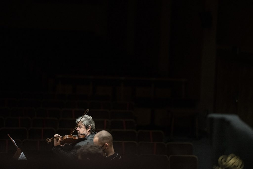 Ciemne zdjęcie. Na środku widoczny mężczyzna grający n skrzypcach. Obok niego siedzi kilka osób.