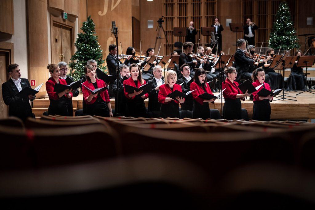 Zdjęcie zrobione z tyłu sceny. Przed sceną stoi Chór Opery i Filharmonii Podlaskiej. Za nimi na scenie siedzi orkiestra.