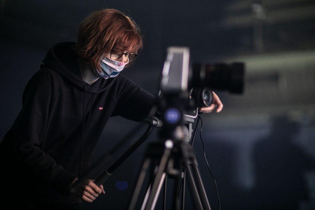Kobieta w maseczce ochronnej stoi przy aparacie na statywie.
