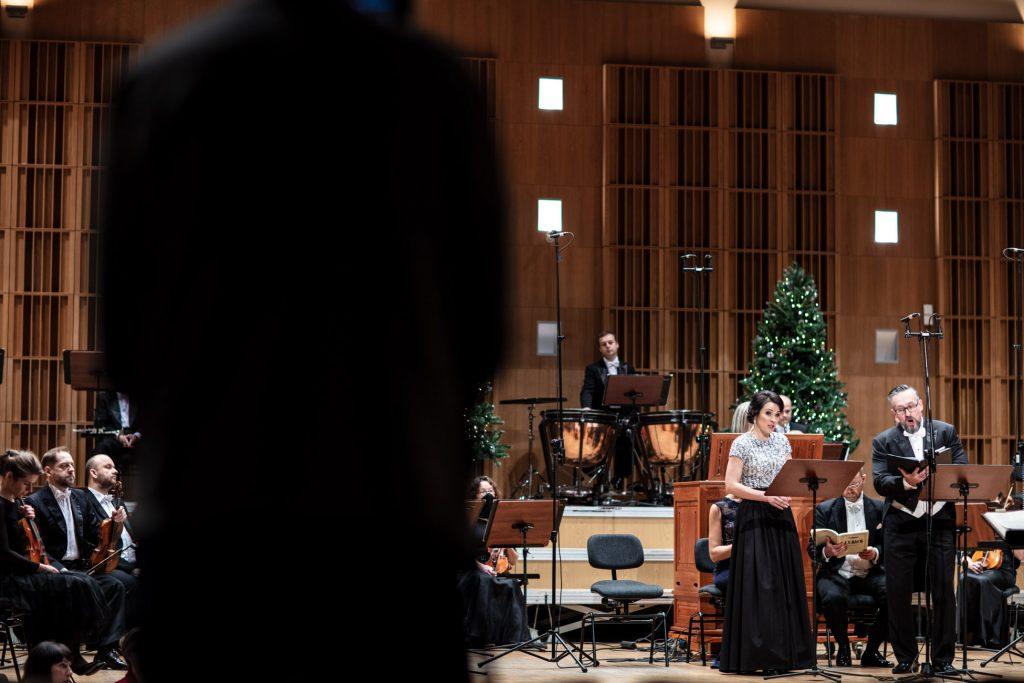 Po prawej stronie przed pulpitami stoi dwójka solistów. Kobieta i mężczyzna. Obydwoje śpiewają. Wokół siedzi orkiestra. Na końcu sceny stoją dwie choinki.