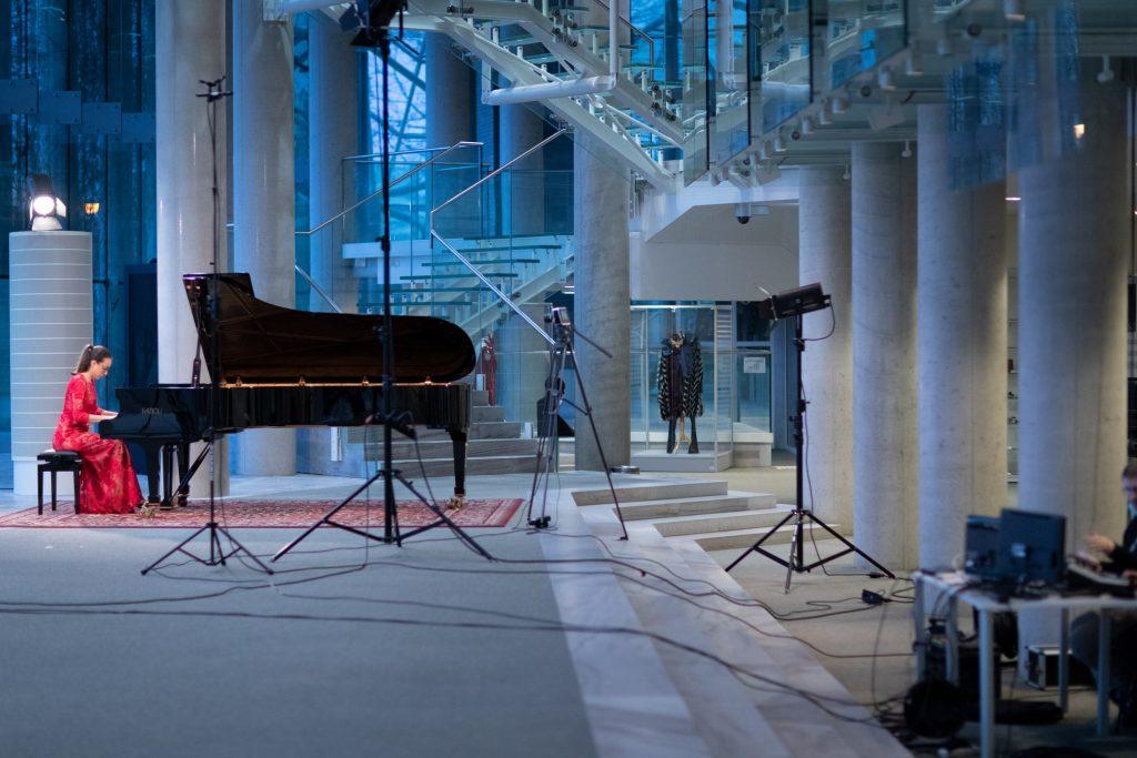 Koncert online transmitowany z dolnego foyer. Kobieta w czerwonej sukni gra na fortepianie. Przed nią statywy z kamerą i reflektorem. Z boku, po prawej stronie, przy stoliku siedzi mężczyzna. Na stole stoją monitory.