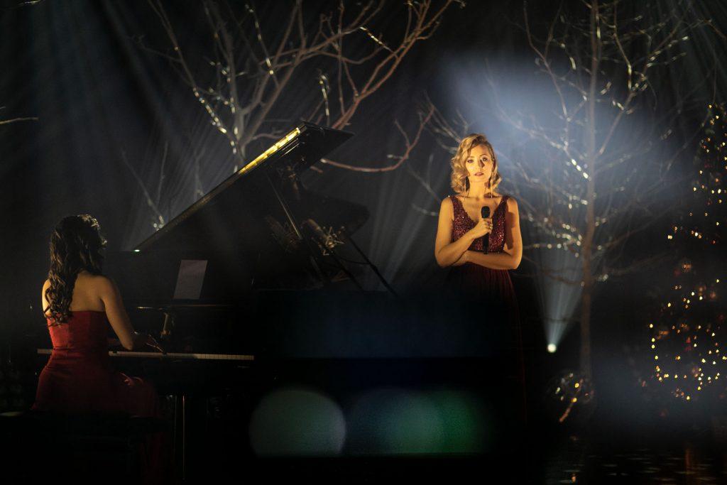 Scena w półmroku. Na scenie dwie kobiety w eleganckich sukniach. Jedna siedzi przy fortepianie, druga stoi obok z mikrofonem. Za nimi łuny białego światła i drzewa bez liści. Po prawej stronie choinka.