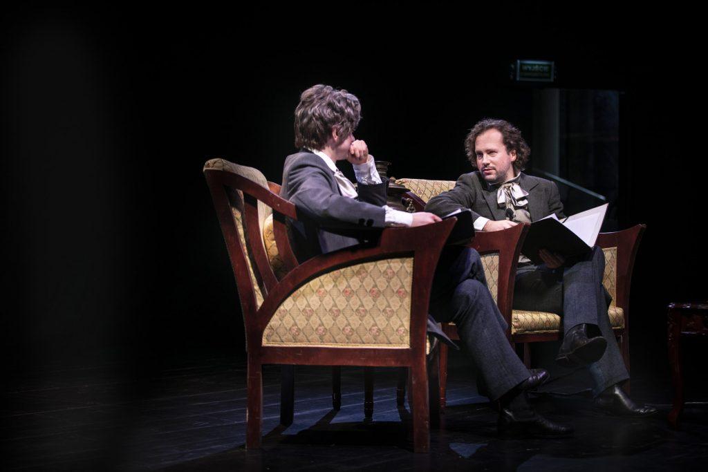 Na stylowych fotelach siedzi dwóch mężczyzn. Ubrani w kostiumy z XIX wieku. Patrzą na siebie. Na kolanach trzymają otwarte, czarne teczki.