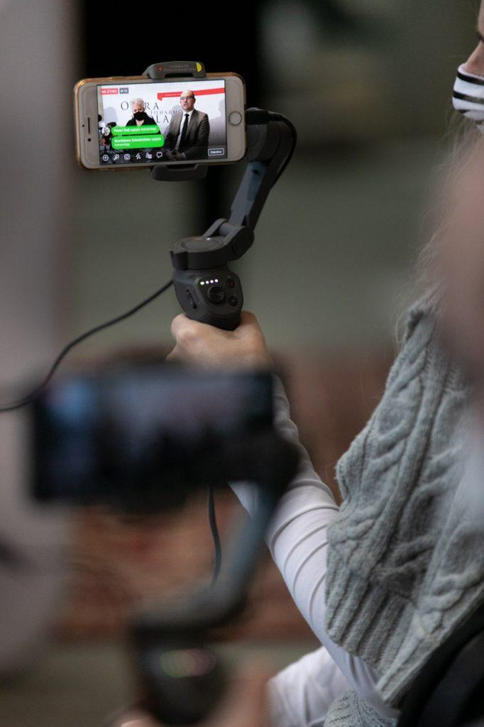 Na zdjęciu ekran telefonu na statywie. Na nim p.o. Dyrektora Opery i Filharmonii Podlaskiej Prof. Violetta Bielecka oraz Marszałek Województwa Podlaskiego, pan Artur Kosicki podczas konferencji prasowej.