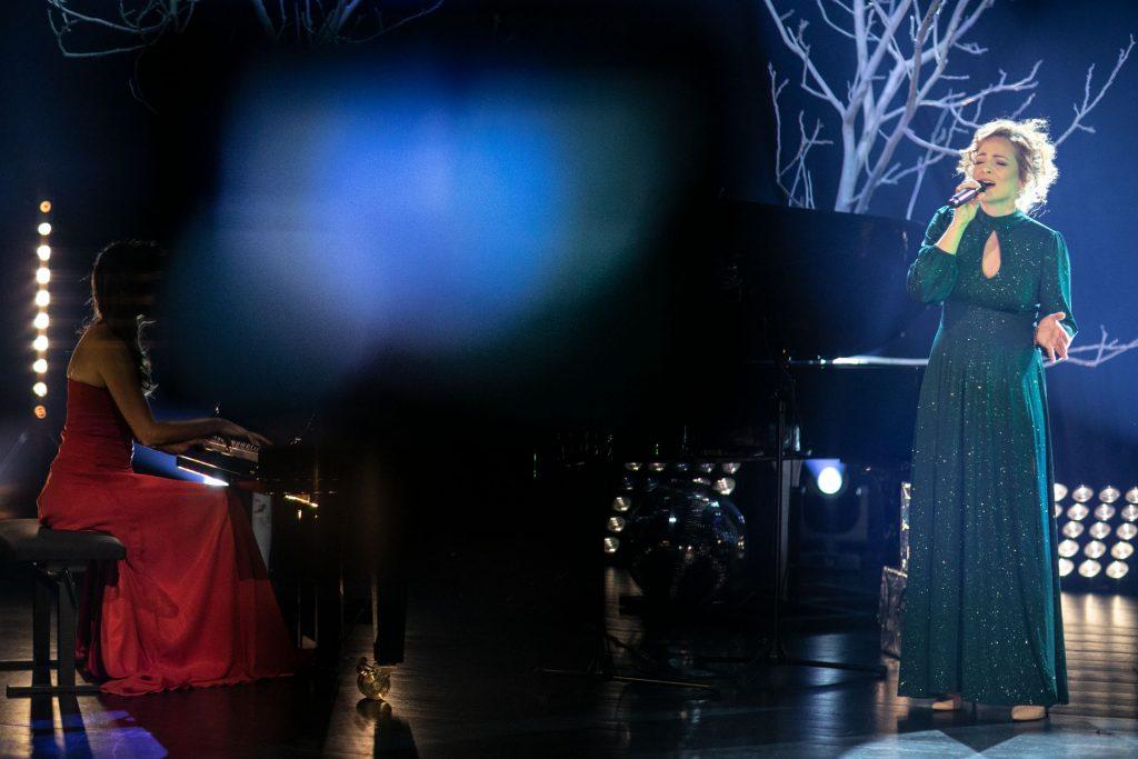 Scena w półmroku. Na scenie dwie kobiety w eleganckich sukniach. Jedna siedzi przy fortepianie, druga stoi obok, śpiewa do mikrofonu. Za nimi drzewa bez liści.