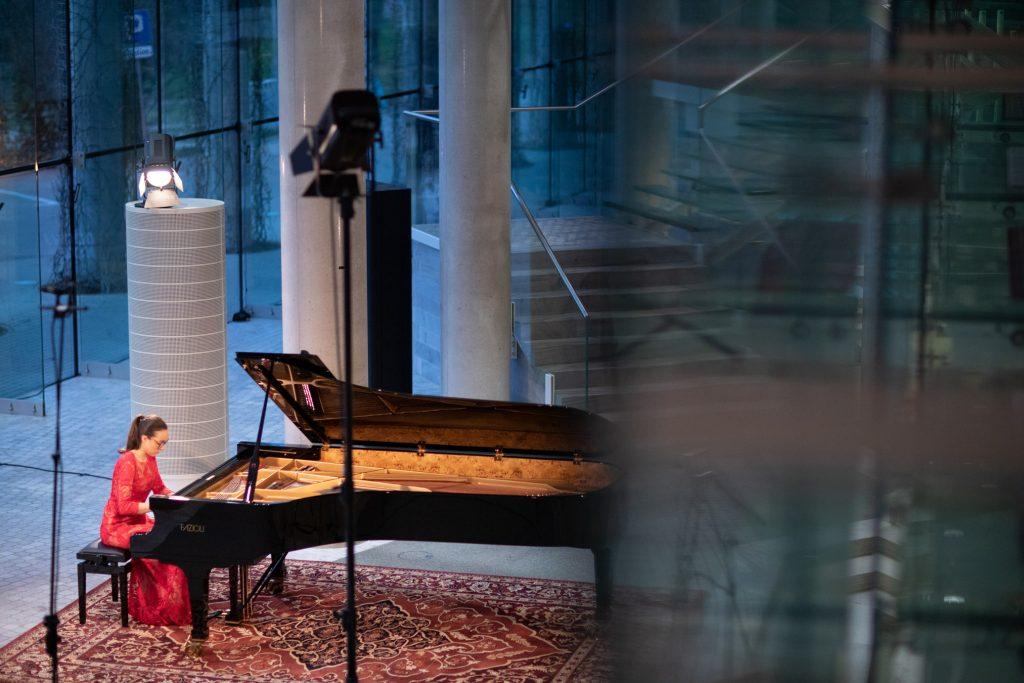 Zdjęcie zrobione z góry. Koncert ma dolnym foyer z cyklu ''Jesień z Chopinem''. Przy fortepianie siedzi kobieta w czerwonej sukni.