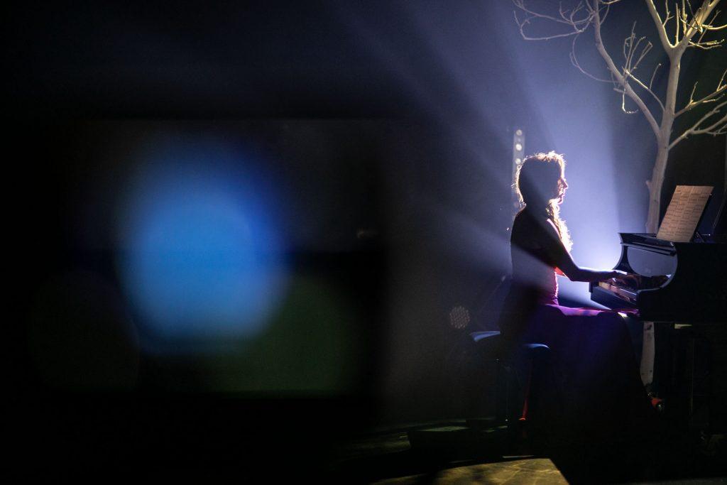 Na scenie półmrok. Przy fortepianie, w łunie białego światła siedzi kobieta. Przy fortepianie stoi drzewo bez liści.
