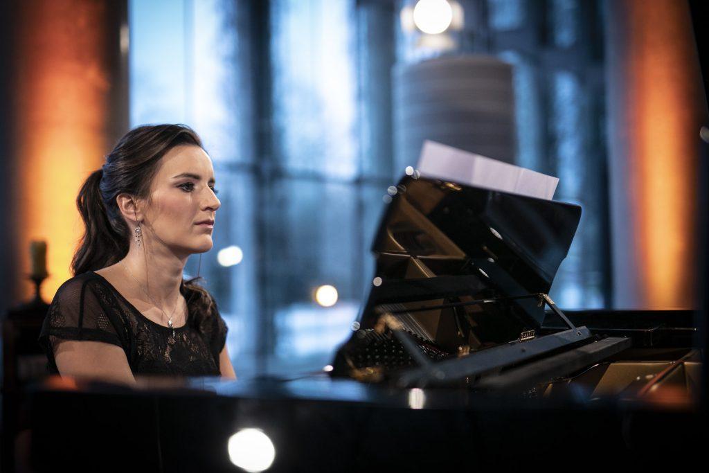 Na dolnym foyer, przy fortepianie siedzi kobieta. Patrzy na nuty rozłożone przed sobą.