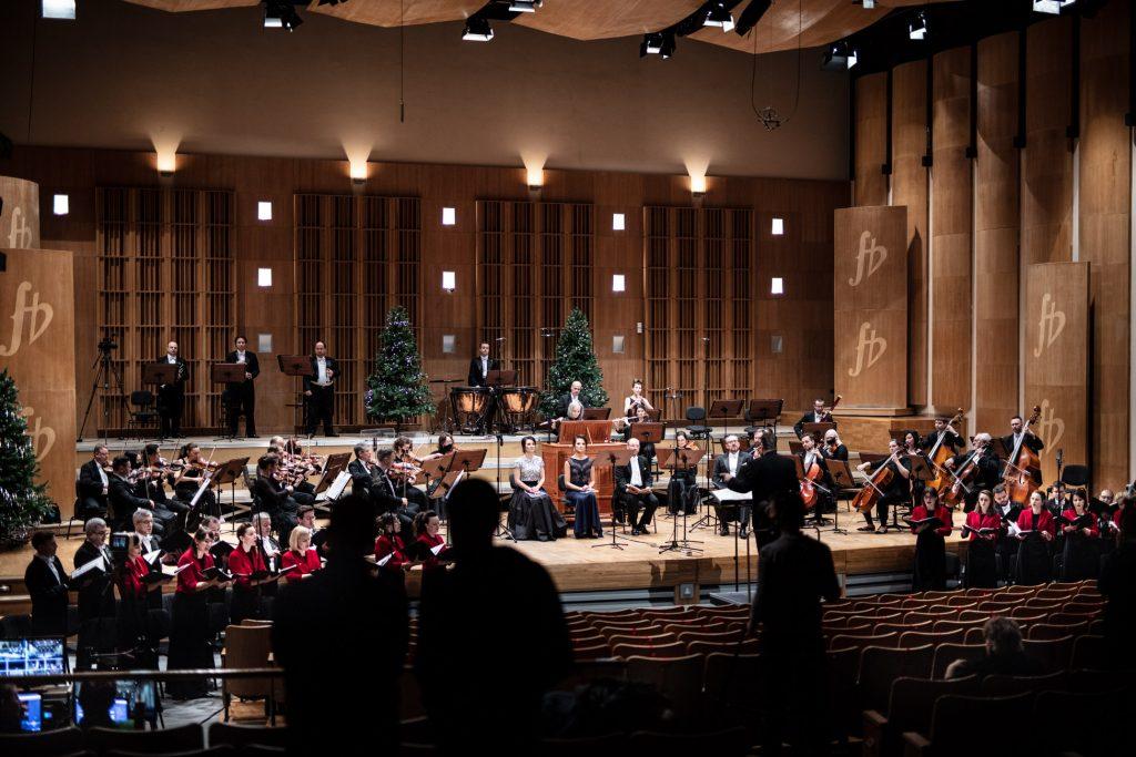 Na scenie gra Orkiestra Opery i Filharmonii Podlaskiej. Na środku siedzi kilku solistów. Przed sceną, po obydwu stronach stoi chór. Na widowni stoi kilka osób. Z tyłu stoi kilka choinek.