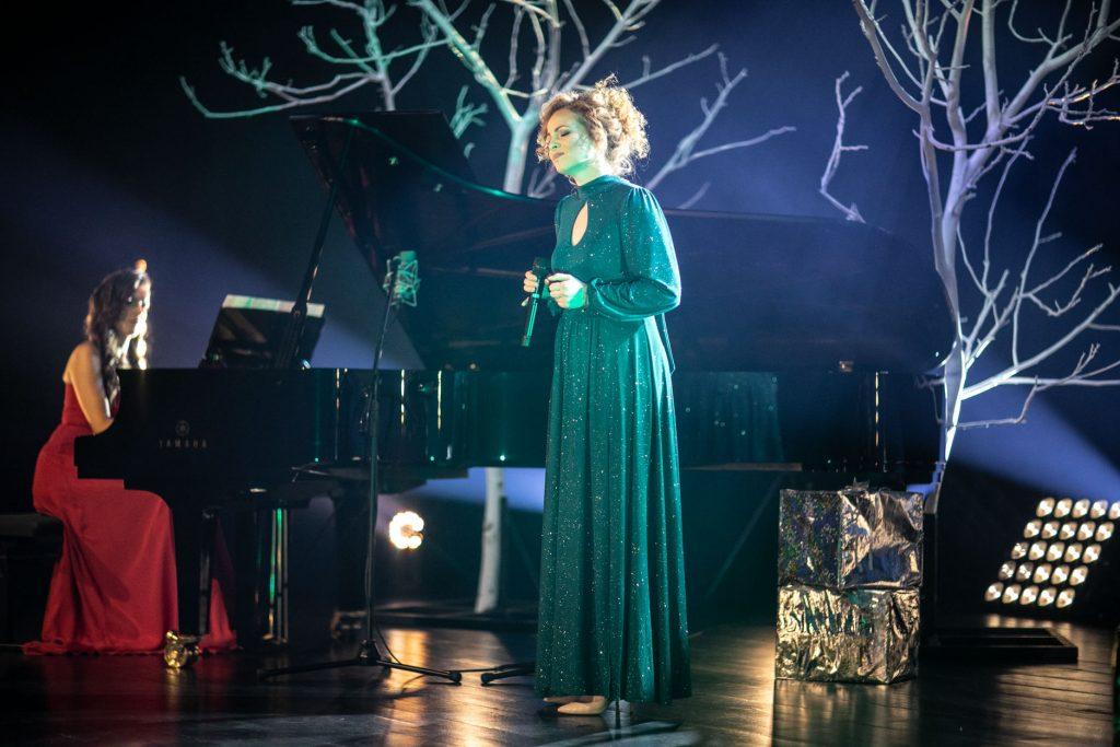 Na scenie dwie kobiety. Jedna, w czerwonej sukni siedzi przy fortepianie. Druga w sukni zielonej stoi z mikrofonem. Obok niej leżą diw srebrne paczki. W oddali drzewa bez liści.
