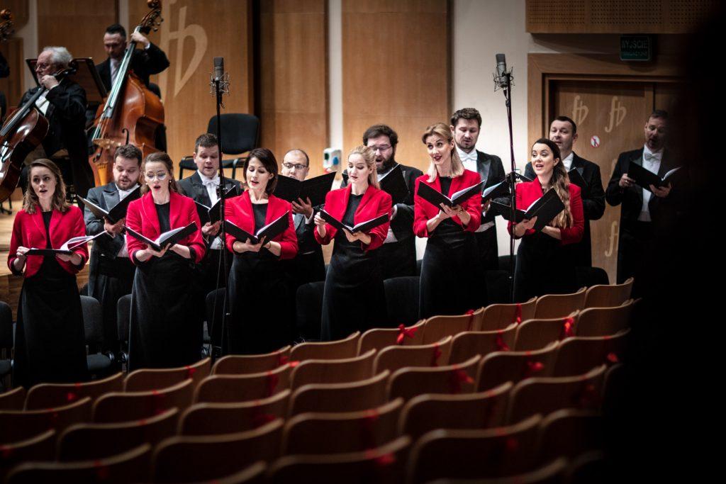Zdjęcie zrobione z tyłu sceny. Przed sceną stoi część Chóru Opery i Filharmonii Podlaskiej. Przed nimi na statywach stoją mikrofony. Krzesła widowni przewiązane czerwonymi wstążkami.