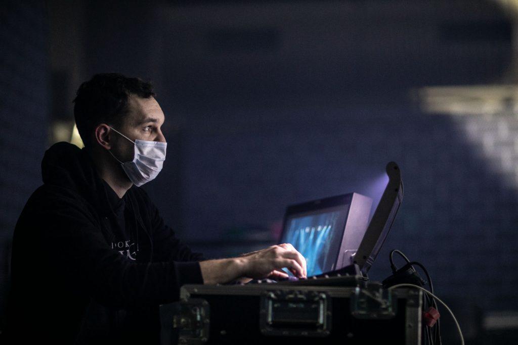 Mężczyzna w maseczce na twarzy siedzi przy monitorach patrząc przed siebie.