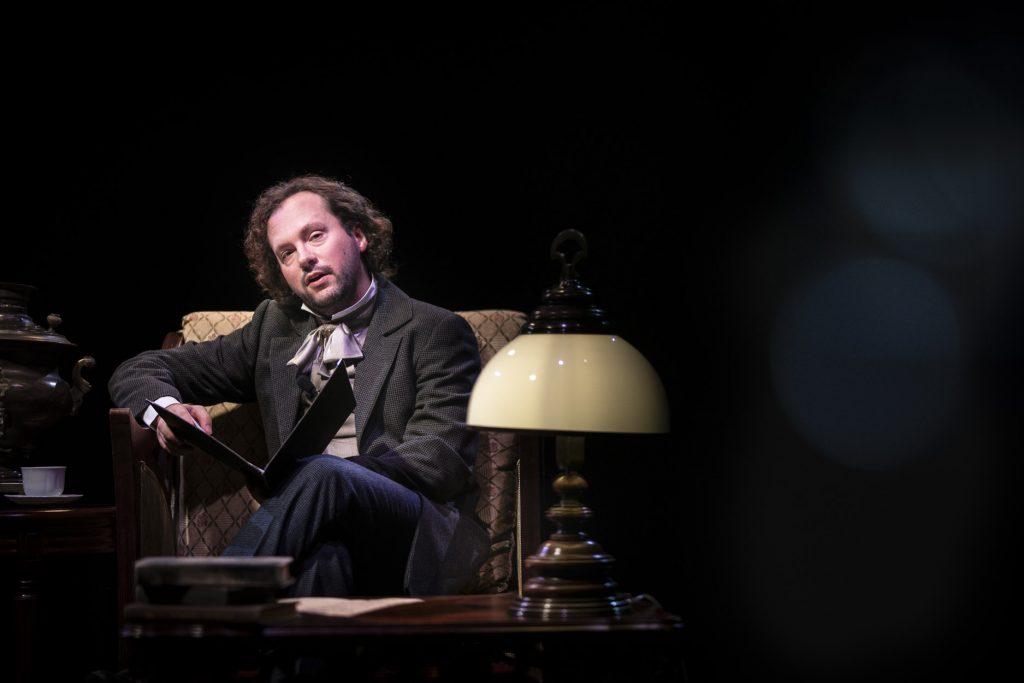 W stylowym fotelu siedzi mężczyzna w stroju z XIX w. Patrzy w obiektyw. Na kolanach trzyma rozłożoną, czarną teczkę. Przed nim stoi drewniany stolik, na nim stylowa lampka.