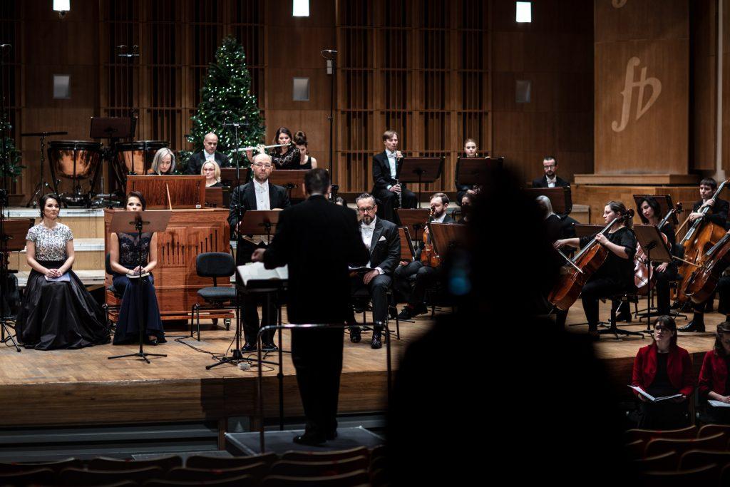 Po lewej stronie siedzą dwie solistki. Po prawej stronie siedzi orkiestra. Przed nimi stoi dyrygent.