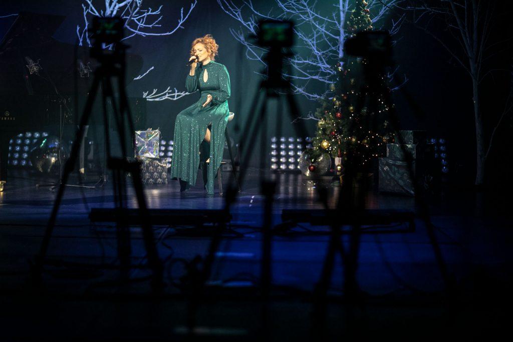 Na scenie półmrok. Na wysokim krześle, na środku sceny siedzi kobieta w eleganckiej sukni. Śpiewa do mikrofonu. Za nią drzewa bez liści podświetlone na niebiesko. Po prawej stronie choinka. Z przodu kilka statywów z kamerami.