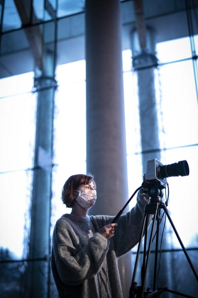 Na zdjęciu kobieta w swetrze, w maseczce ochronnej stoi z aparatem na statywie.