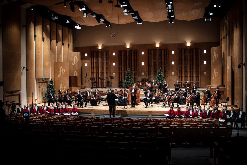 Widok z końca sali. Na scenie siedzi orkiestra. Pośród nich siedzą soliści. Przed sceną siedzi chór. Wszyscy trzymają otwarte nuty. Na środku, przed pulpitem stoi dyrygent.