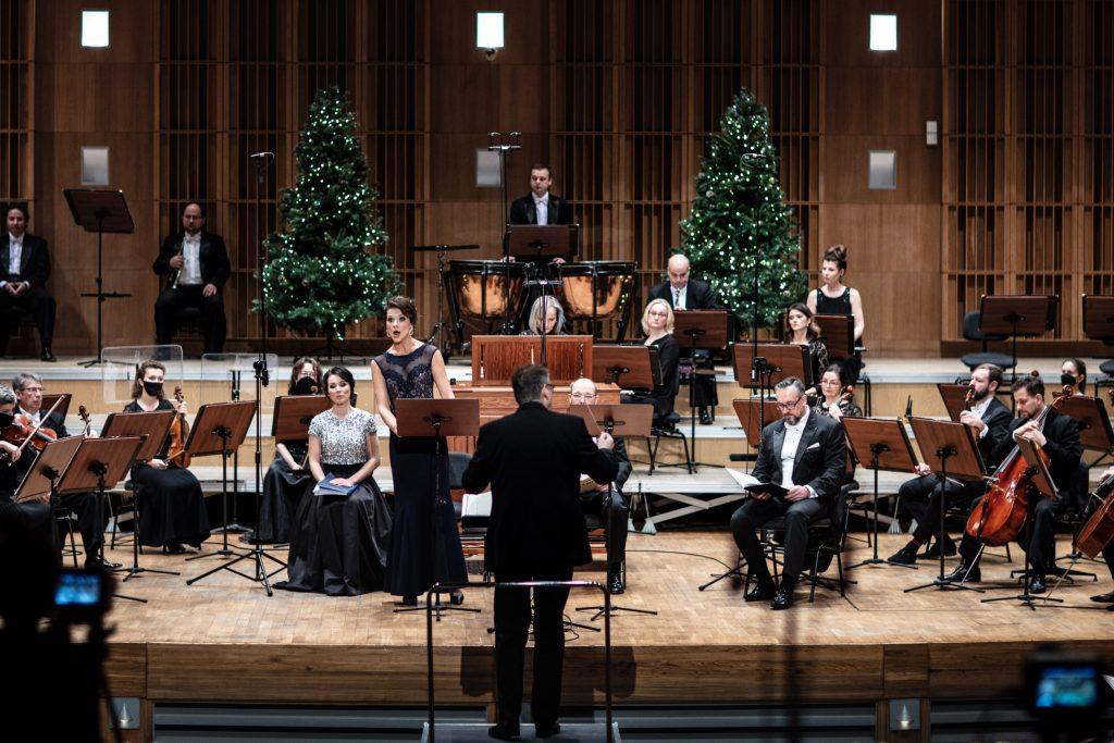 Na scenie Orkiestra i Filharmonia Podlaska. Na środku stoi solistka w długiej sukni. Tyłem na podeście stoi dyrygent. Z tyłu stoją dwie choinki.