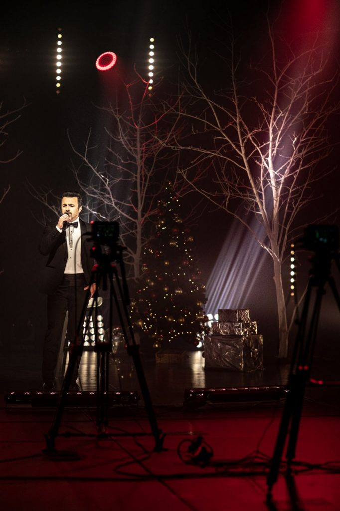 Na scenie półmrok. Po lewej stronie stoi mężczyzna w smokingu. Śpiewa do mikrofonu. Dalej stoją dwa drzewa bez liści. Pomiędzy nimi choinka, i pudełka zapakowane w błyszczący papier. W oddali z reflektorów świeci do góry białe światło. Na przodzie stoi kamera na statywie.
