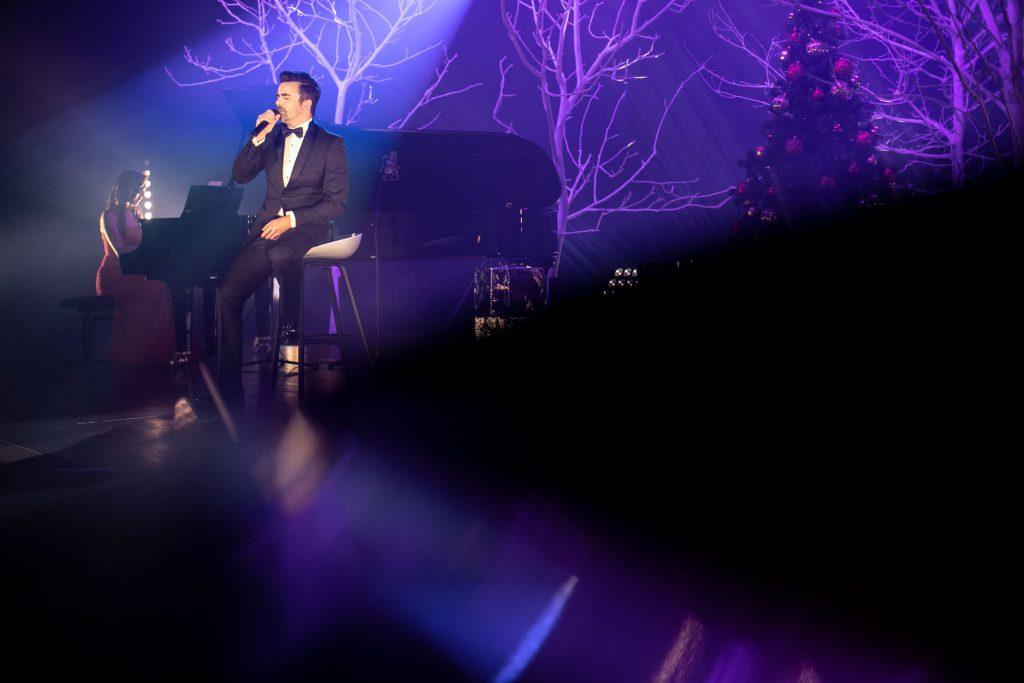 Scena oświetlona niebieskim światłem. Na środku, na wysokim krześle, siedzi mężczyzna w czarnym garniturze. Śpiewa do mikrofonu. Za nim, przy fortepianie, siedzi kobieta w długiej, czerwonej sukni. W oddali widać drzewa bez liści. Pomiędzy nimi stoi choinka z bombkami.