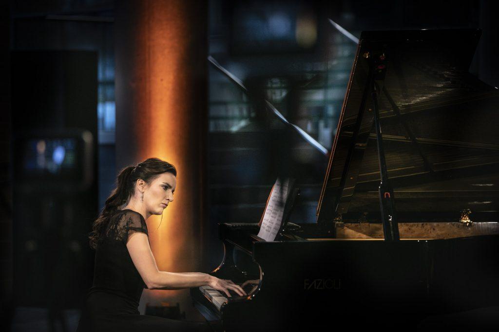 Koncert na dolnym foyer. Na fortepianie gra kobieta w czarnej sukni.