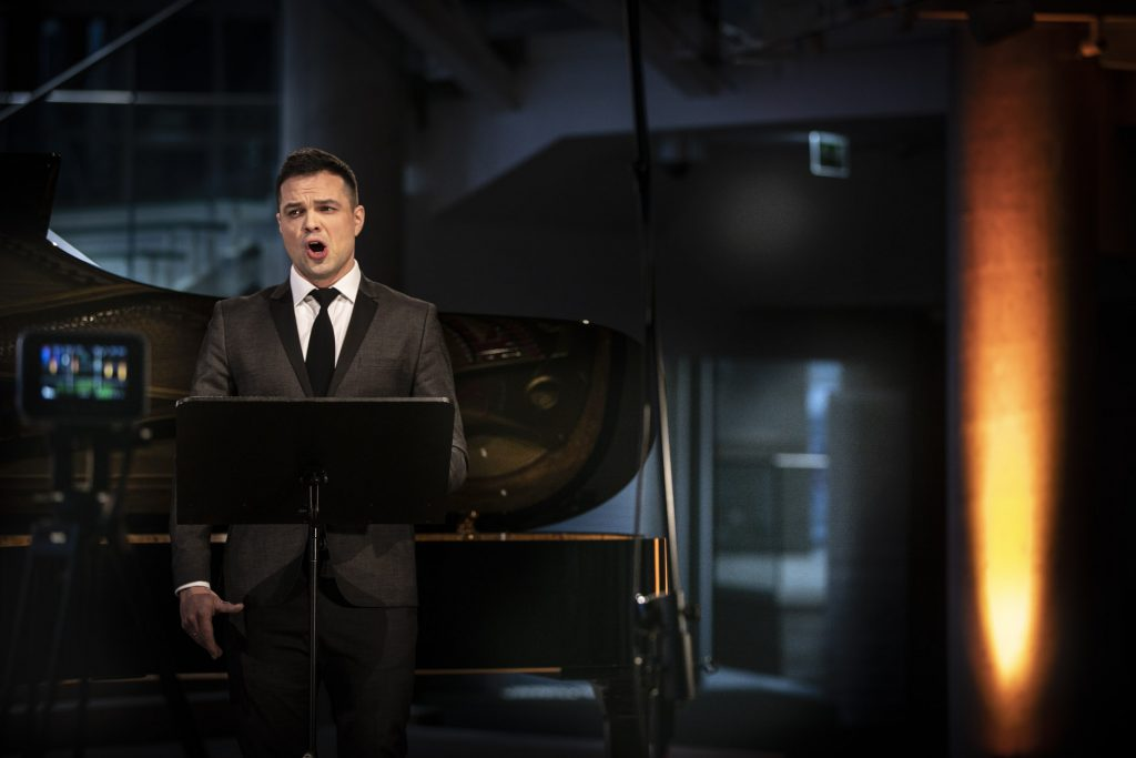 Koncert online na dolnym foyer. Mężczyzna w garniturze stoi przed pulpitem z nutami. Śpiewa. Za nim fortepian.