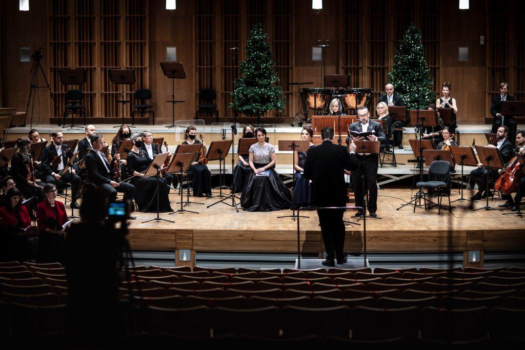 Widok z końca sali. Na scenie siedzi orkiestra. Pośród nich siedzą soliści. Na środku, przed pulpitem stoi dyrygent. W oddali stoją dwie choinki.