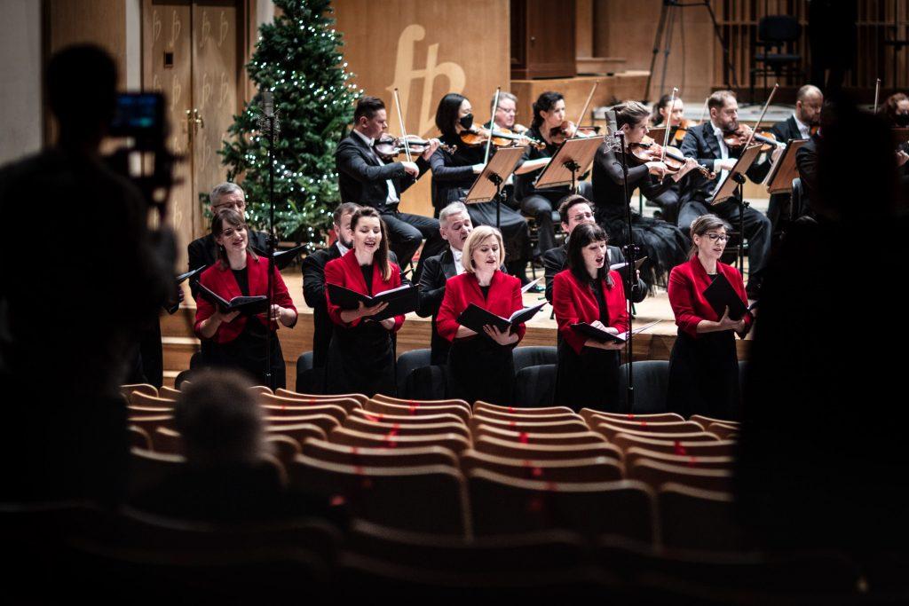 Zdjęcie zrobione z końca widowni. Przed sceną stoi Chór Opery i Filharmonii Podlaskiej. Za nimi na scenie gra orkiestra.