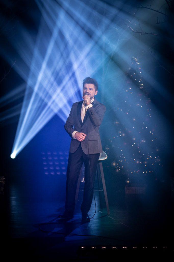 Scena oświetlona niebiesko-białym światłem. Na środku stoi mężczyzna w garniturze. Śpiewa do mikrofonu. Za nim widać gałęzie drzew. Dalej stoi choinka ze świecącymi lampkami.