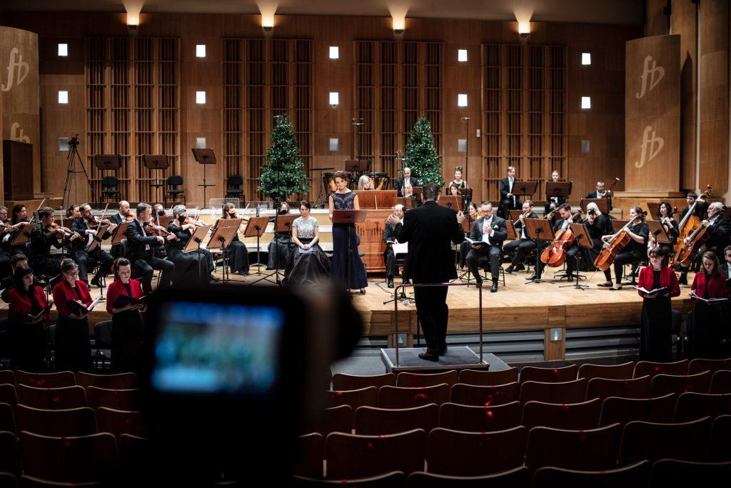Widok z końca sali. Na scenie siedzi orkiestra. Pośród nich siedzą soliści. Przed sceną po obydwu stronach stoi chór. Wszyscy trzymają otwarte nuty. Na środku, przed pulpitem stoi dyrygent.