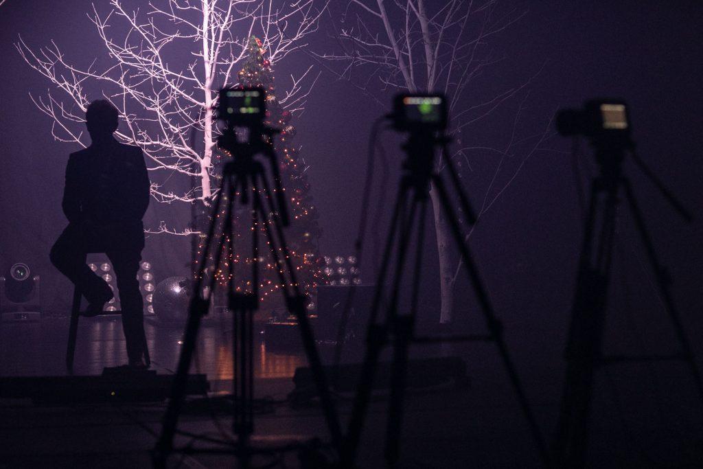 Scena w półmroku. Z przodu stoją trzy statywy z kamerami. Na scenie, na wysokim krześle siedzi mężczyzna. Za nim widać drzewa bez liści podświetlone jasnym światłem. Pomiędzy nimi stoi choinka z zapalonymi na niej lampkami.