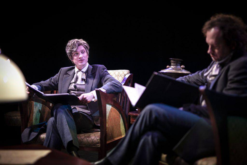 Na scenie, w stylowych fotelach siedzi dwóch mężczyzn w strojach z XIX wieku. Na kolanach trzymają rozłożone teczki z kartkami. Pomiędzy nimi stoi stylowy stolik, na nim lampa.