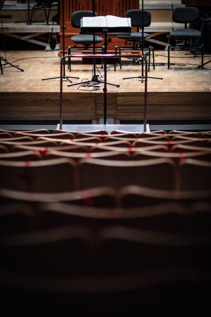 Zdjęcie zrobione z końca sali. Na zdjęciu widoczne krzesła widowni, przewiązane czerwonymi taśmami. Pod sceną stoi podest. Na scenie widać trzy puste krzesła.