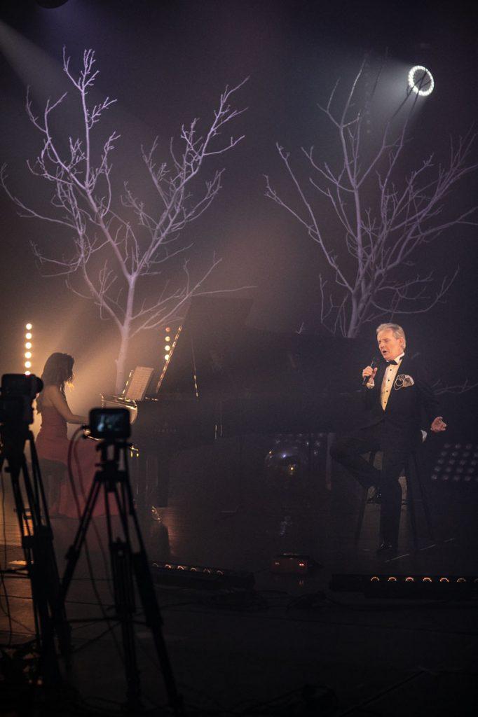 Scena w półmroku, oświetlona delikatnym jasnym światłem. W prawym, górnym rogu widać okrągłą, świecącą lampkę imitującą księżyc. Na wysokim krześle siedzi mężczyzna w czarnym garniturze. Śpiewa do mikrofonu. Obok , przy fortepianie siedzi kobieta w czerwonej sukni. Z przodu widać dwa statywy na których widać kamery.