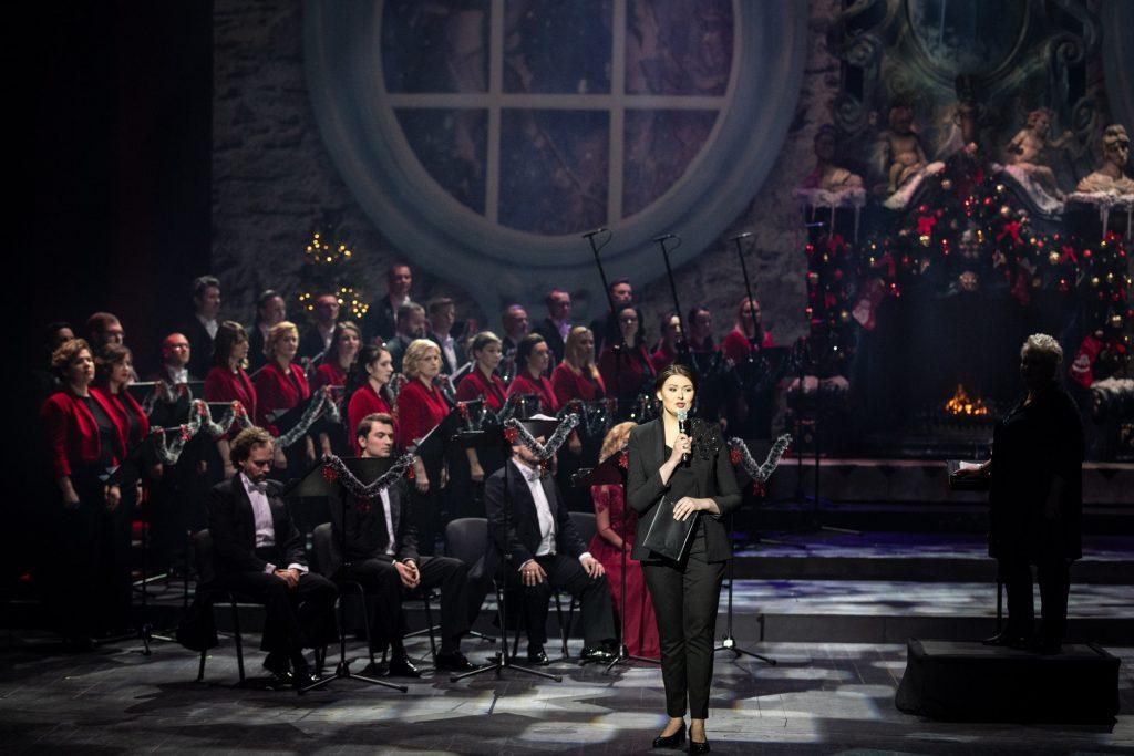 Po lewej stronie na krzesłach siedzą soliści koncertu. Za nimi stoi Chór Opery i Filharmonii Podlaskiej. Z przodu, z mikrofonem stoi kobieta. Po prawej stronie na podeście stoi kierownik chóru. W tle widać ogień palący się w kominku.