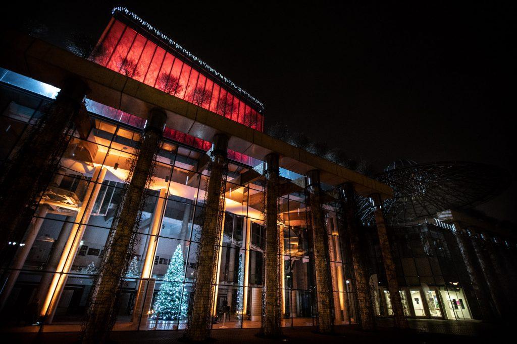 Podświetlony na czerwono gmach Opery i Filharmonii Podlaskiej. Zdjęcie zrobione wieczorem. W środku, za szybami, widać choinki.