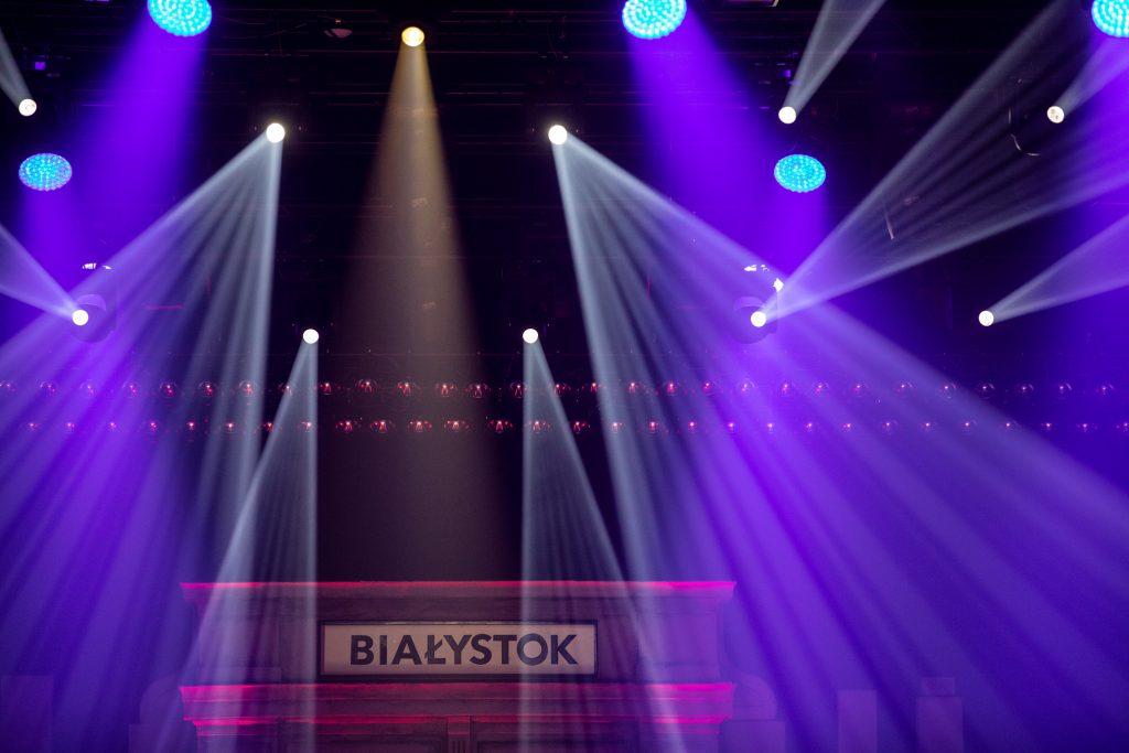 Scena w półmroku. Z góry kilkanaście reflektorów oświetla scenę. Z przodu część scenografii i napis ''Białystok''.