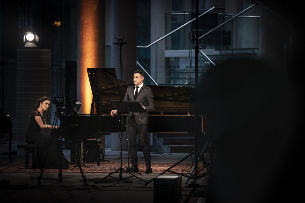 Koncert online na dolnym foyer. Przy pulpicie stoi mężczyzna w garniturze. Obok, przy fortepianie siedzi kobieta w czarnej sukni. Przed nimi statyw z aparatem.