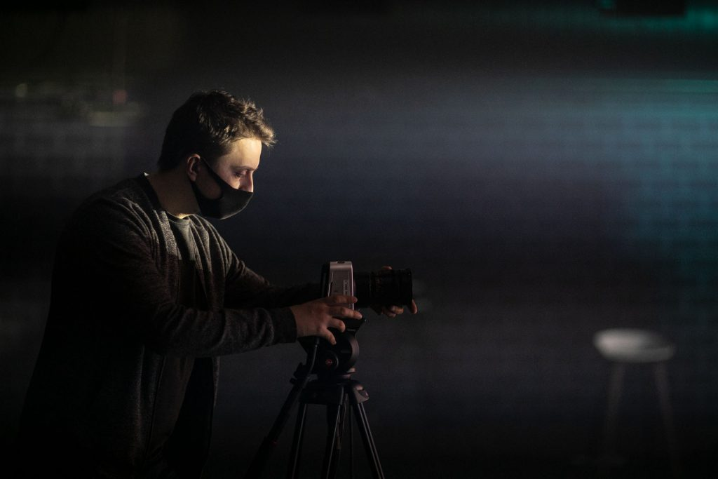 Mężczyzna w maseczce ochronnej stoi przy kamerze na statywie.