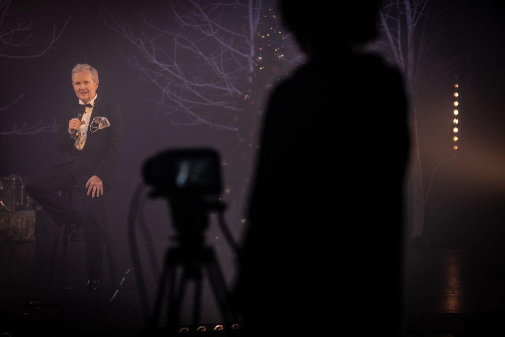 Na scenie , na wysokim krześle siedzi mężczyzna. W ręku trzyma mikrofon. W tle widać gałęzie drzew. Z przodu widoczny cień człowieka, przed którym stoi aparat na statywie.